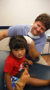 Dr. Cedric Hayden and a young patient in Chuuk Micronesia